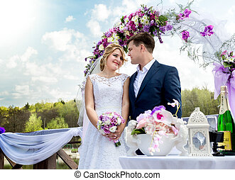 bride and groom standing under floral arch at sunny day