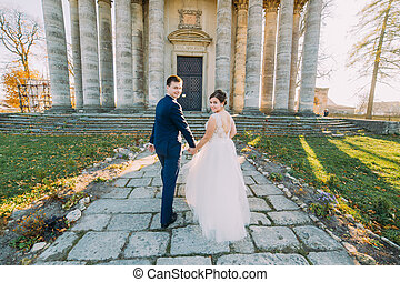 Beautiful bride and groom walking holding hands in front of old building with columns