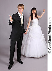 Beautiful bride and groom welcome in studio on gray background; bride stands behind groom; focus on man