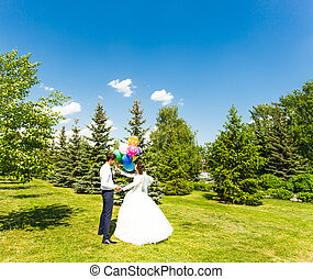 Beautiful bride and groom with colorful balloons