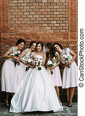 Beautiful bride and the bridesmaids with the bouquets