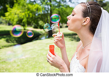 Beautiful bride blowing bubbles in garden