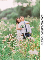 Beautiful bride embracing from behind her handsome groom in the summer meadow with wild flowers on foreground