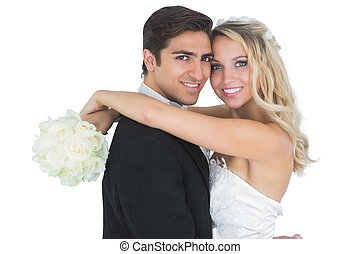 Beautiful bride embracing her husband holding a white...