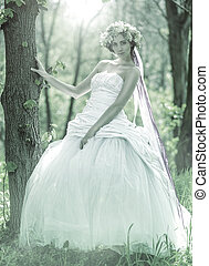 Beautiful bride , flower tiara on her head , relying on the tree , monochrome