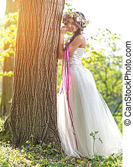 Beautiful bride , flower tiara on her head , relying on the tree