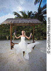 Beautiful bride flying on nice tropical swing.