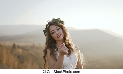 Beautiful bride girl in a long white dress and with a bouquet in her hand standing in the field against the background of the mountains and pine forest on the sunset