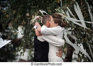 beautiful bride hugging groom at wedding ceremony