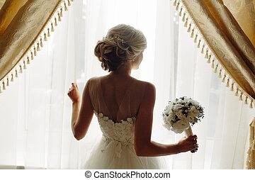 beautiful bride in a wedding dress, by window.