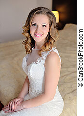 Beautiful bride in a white dress sitting