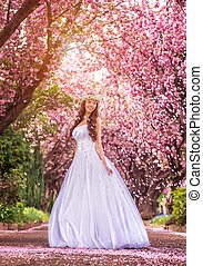 Beautiful bride in a white dress under the sakura tree and flower petals
