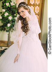 Beautiful bride in elegant white wedding dress and veil with long curly hair posing indoors