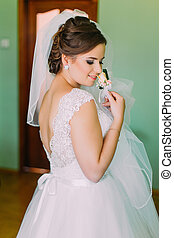 Beautiful bride in lace wedding dress standing with his back to the camera.