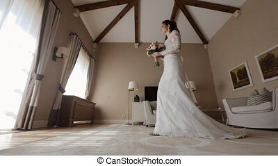 Beautiful bride in the wedding dress going to the window in the hotel room