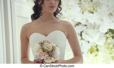 Beautiful bride in wedding dress with flowers in a studio