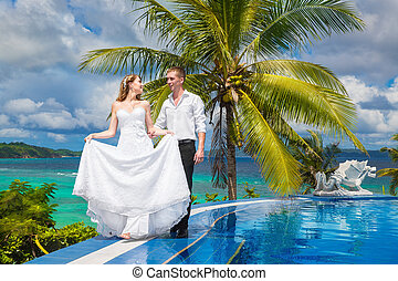 Beautiful bride in wedding dress with long train and groom standing at the infinity pool in the hotel on a tropical island. Wedding and honeymoon.