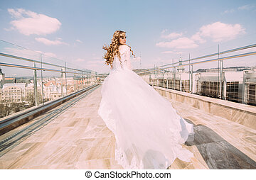 Beautiful bride in white dress dancing on roof against the backdrop of cityscape