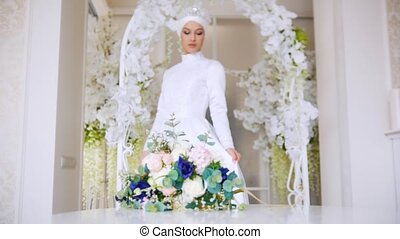 Beautiful bride in white traditional muslim dress with bunch...