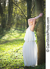 Beautiful bride in white wedding dress leaning against tree outdoors