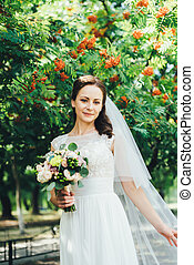 beautiful bride in white wedding dress outdoors