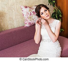 Beautiful bride in white wedding dress puts on earring. Beauty model girl is wearing jewelry.