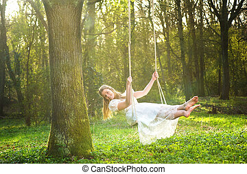 Beautiful bride in white wedding dress smiling and swinging in the forest