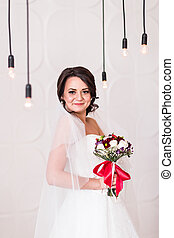 Beautiful bride in white wedding dress with bridal bouquet