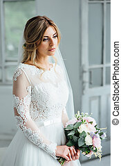 Beautiful bride in white wedding dress with a wedding bouquet standing near the wooden door