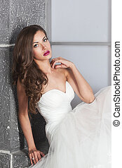 beautiful bride in white wedding dress with hairstyle and bright makeup