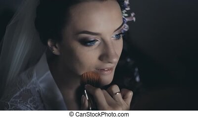 Beautiful bride in with white veil talking while make-up...