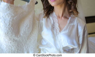 Beautiful bride is embracing wedding dress and smiling