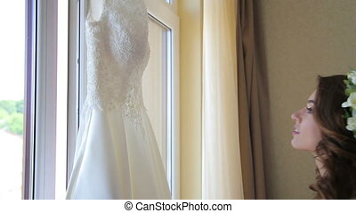 Beautiful bride is embracing wedding dress
