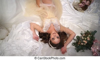 Beautiful bride is surrounded by wedding dresses, look straight into the camera, big beautiful eyes.