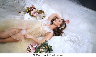 Beautiful bride is surrounded by wedding dresses.