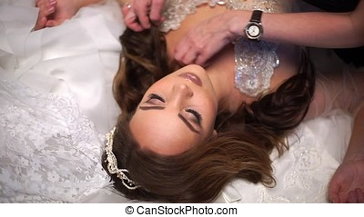 Beautiful bride is surrounded by wedding dresses, make-up artist corrects hair.