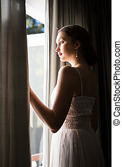 Beautiful bride looking through window while standing in ...