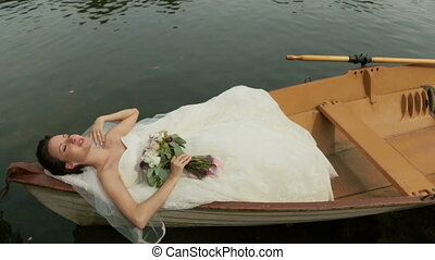 Beautiful bride lying in the boat on the lake. Paris, France