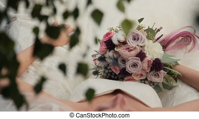 Beautiful bride lying with wedding bouquet in hands