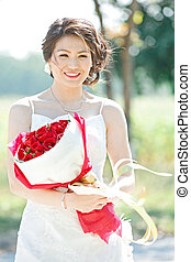 beautiful bride outdoors with rose bouquet