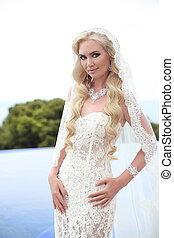 Beautiful Bride Portrait wedding makeup and wavy hairstyle, girl in white veil, jewelry model, fashion bride gorgeous beauty, smiling happy bride woman. outdoor photo portrait.