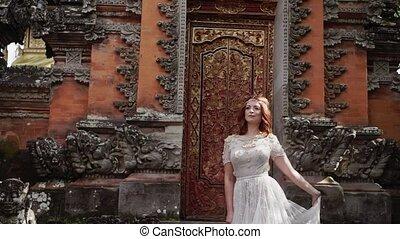 Beautiful bride posing near buddhist temple in Bali. Walking...