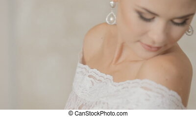 Beautiful bride posing on the background of wall indoors