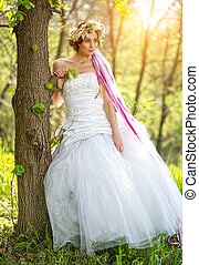 Beautiful bride  relying on tree