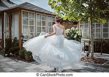Beautiful bride running away in the garden