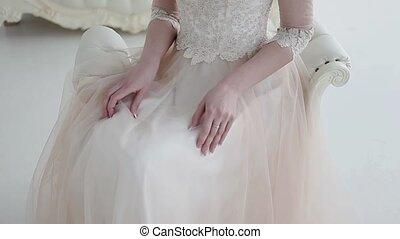 Beautiful bride sitting on a chair, a lush lace skirt...