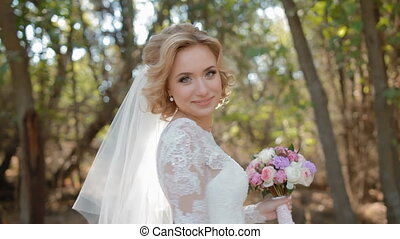 Beautiful caucasian bride spinning around holding her wedding dress and bouquet.