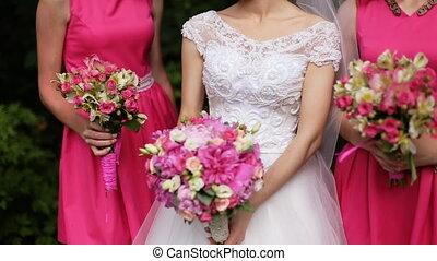 Beautiful bride standing between bridesmaids in pink dresses...