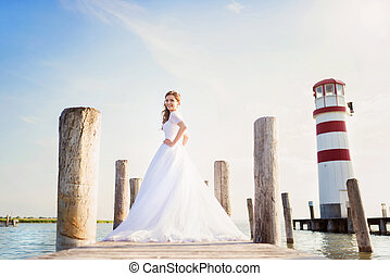 Beautiful bride standing in front of lighthouse