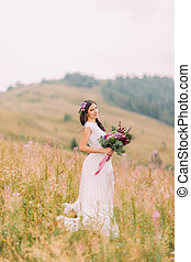 Beautiful bride standing with bouquet on the field in Alpian mountains